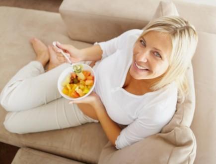 אישה בהריון יושבת על ספה ואוכלת פירות (צילום: Jacob Wackerhausen, Istock)