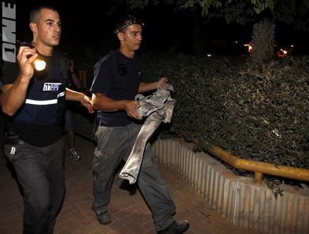 שוטרים מסלקים שרידי הפצצה באופקים (רויטרס) (צילום: מערכת ONE)