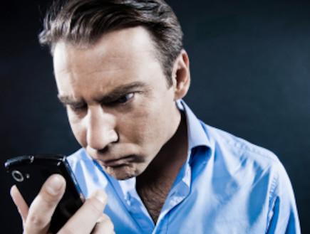 גבר מסתכל על טלפון סלולרי (צילום: OSTILL, Istock)
