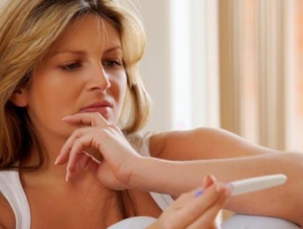 אישה מוטרדת מתבוננת בבדיקת הריון (צילום: Dean Mitchell, Istock)