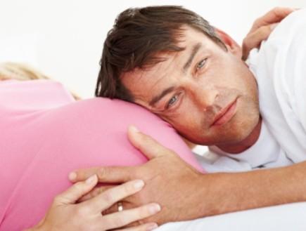 גבר מניח ראש על בטן הריונית (צילום: GlobalStock, Istock)