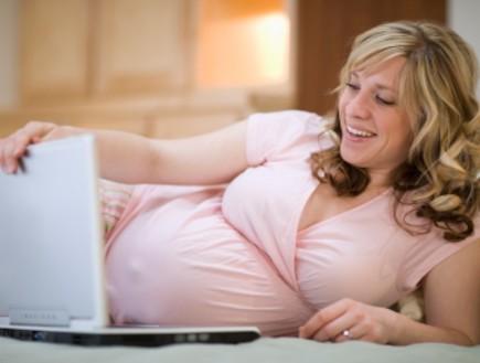 אישה בהריון שוכבת על המיטה מול מחשב נייד (צילום: istockphoto)
