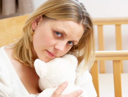 אישה עצובה מביטה אל המצלמה שמאחוריה מיטת תינוק ריק (צילום: Cathy Yeulet, Istock)