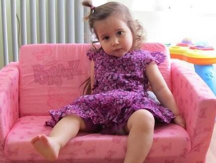 אלה שרצקי בשמלה סגולה יושבת על ספה ורודה (צילום: תומר ושחר צלמים)