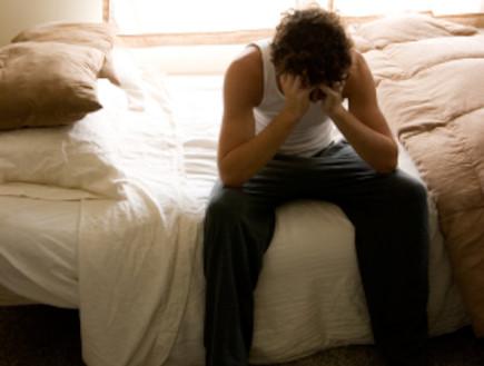 יושב על המיטה ותופס את הראש (צילום: Forest Woodward, Istock)