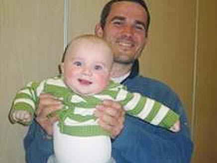 """אשר פלמר ובנו התינוק ז""""ל (צילום: באדיבות המועצה המקומית קרית ארבע)"""