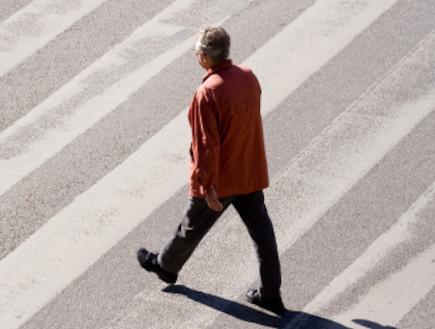 גבר הולך בכביש (צילום: istockphoto)