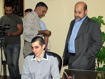 אבו מרזוק מתבונן בשליט בזמן הריאיון לטלוויזיה המצר (צילום: AP)