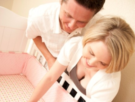 הורים מניחים תינוקת במיטה (צילום: istockphoto)