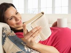 אישה בהריון קוראת ספר ומחזיקה כוס (צילום: istockphoto)