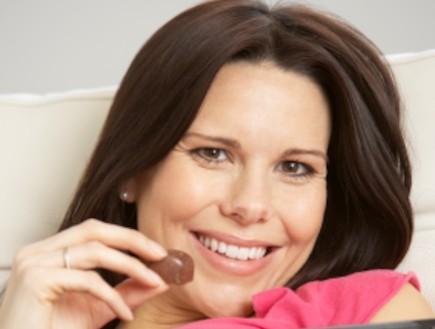 אישה בהריון אוכלת שוקלד (צילום: Mark Bowden, Istock)