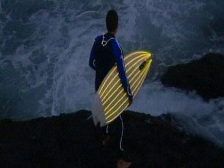 צפו: גלישה לאור חליפות ניאון (צילום: רויטרס)