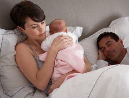 אמא מחזיקה תינוקת במיטה אבא ישן, אחרי לידה