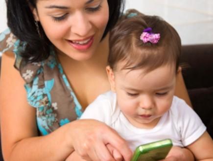 אמא וילדה משחקות באייפון (צילום: apomares, Istock)