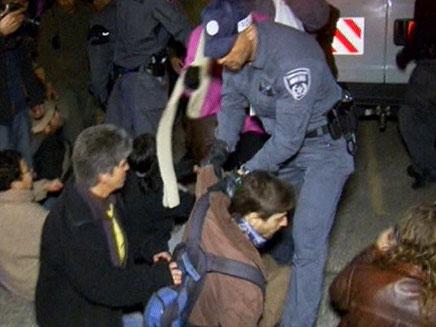 שוטרים עוצרים מפגין, הערב
