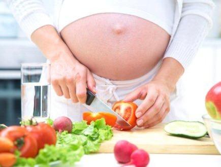 אישה בהריון מבשלת במטבח (צילום: ThinkStock)