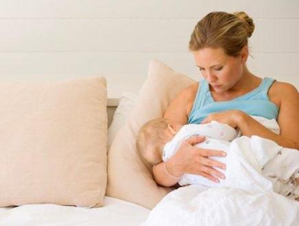 אמא מניקה תינוק על הספה