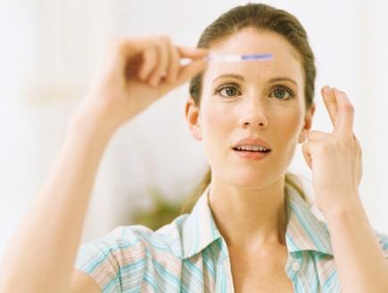 אישה מתבוננת בבדיקת הריון מחזיקה אצבעות