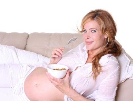 אישה בהריון שוכבת על ספה ואוכלת (צילום: אימג'בנק / Thinkstock)