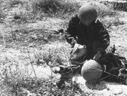 """לוחם מטפל בפצוע בגבעת התחמושת (צילום: אתר צה""""ל, ויקיפדיה)"""