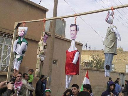 תולים את בובותיהם של האחים אסד (צילום: רויטרס)