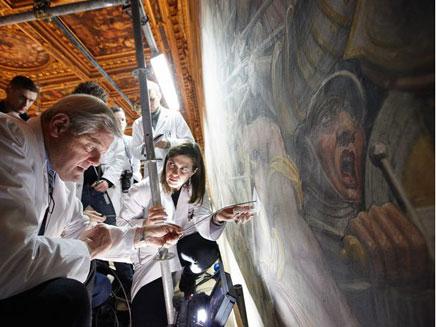 מדענים בוחנים את הציור (צילום: נשיונל ג'אוגרפיק)