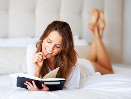 קוראת ספר במיטה