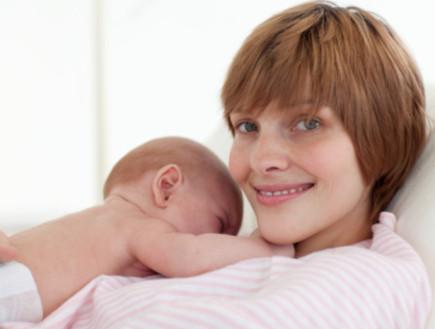 אמא יושבת במיטה עם תינוק אחרי הלידה (צילום: אימג'בנק / Thinkstock)