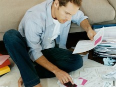 בחור מסתכל על ניירת (צילום: אימג'בנק / Thinkstock)