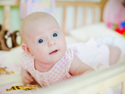 תינוקת במיטה מרימה ראש (צילום: אימג'בנק / Thinkstock)