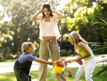 אמא מתוסכלת עומדת מול שני ילדים שרבים (צילום: אימג'בנק / Thinkstock)