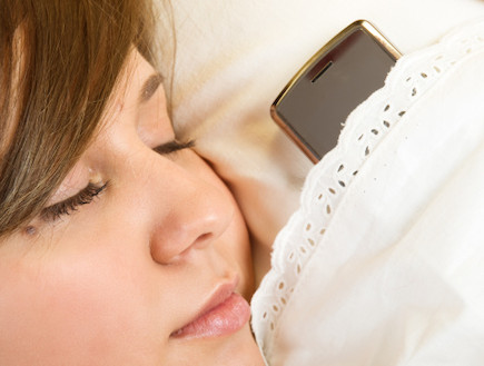 ישנה עם טלפון סלולרי