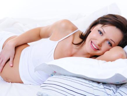 אישה בהריון שוכבת על כרית (צילום: אימג'בנק / Thinkstock)
