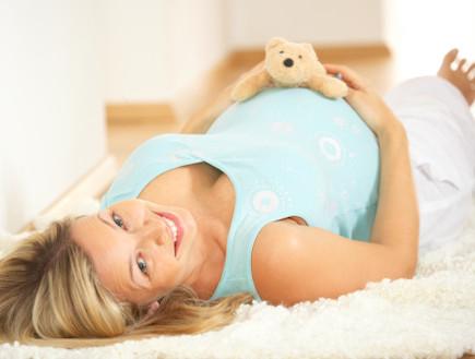 אישה בהריון עם דובי על הבטן