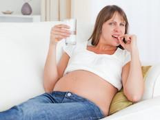 אישה בהריון לוקחת תרופה מחזיקה כוס מים (צילום: אימג'בנק / Thinkstock)