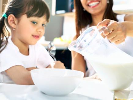 אמא נותנת לילדה שלה חלב