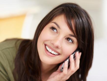 אישה מחייכת עם טלפון סלולרי (צילום: אימג'בנק / Thinkstock)