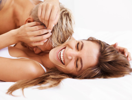 גבר ואישה צוחקת במיטה