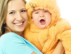 אמא בחולצה קצרה מחזיקה תינוק עם חרמונית (צילום: אימג'בנק / Thinkstock)