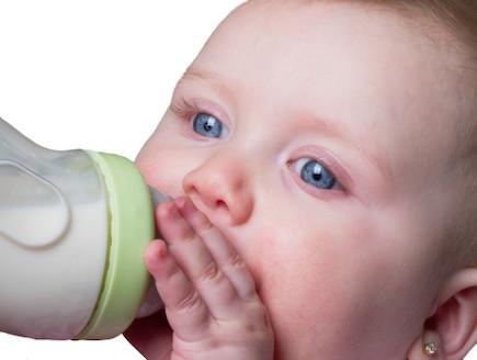 תינוקת תופסת פטמה של בקבוק (צילום: אימג'בנק / Thinkstock)