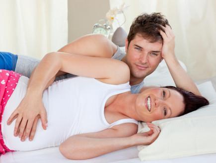גבר ואישה בהריון שוכבים מחובקים במיטה (צילום: אימג'בנק / Thinkstock)