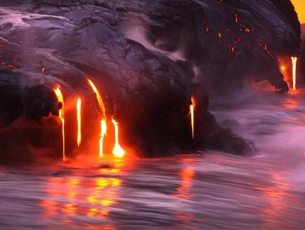 הר וולקני מתפרץ על שפת הים בהוואי