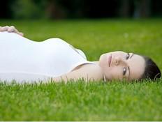 אישה בהריון שוכבת על הדשא (צילום: אימג'בנק / Thinkstock)