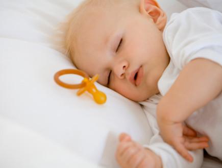 תינוק ישן עם מוצץ לידו