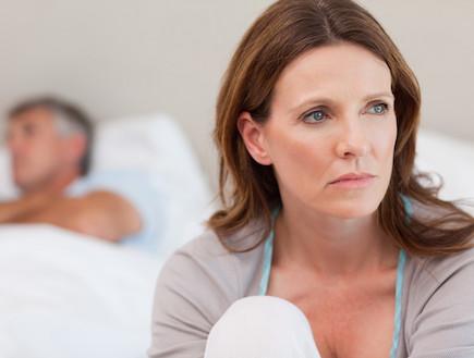 אישה עצובה במיטה וגבר ברקע