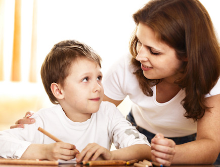ילד כותב מביט לעבר אמו