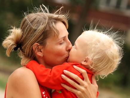 אמא מחבקת ומנשקת ילד