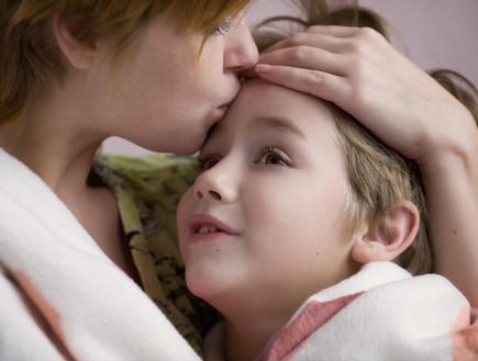אמא מנשקת ילד במצח