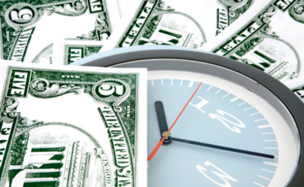 שעון בתוך שטרות כסף (צילום: אימג'בנק / Thinkstock)