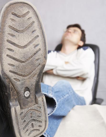 גבר יושב ומציג נעל